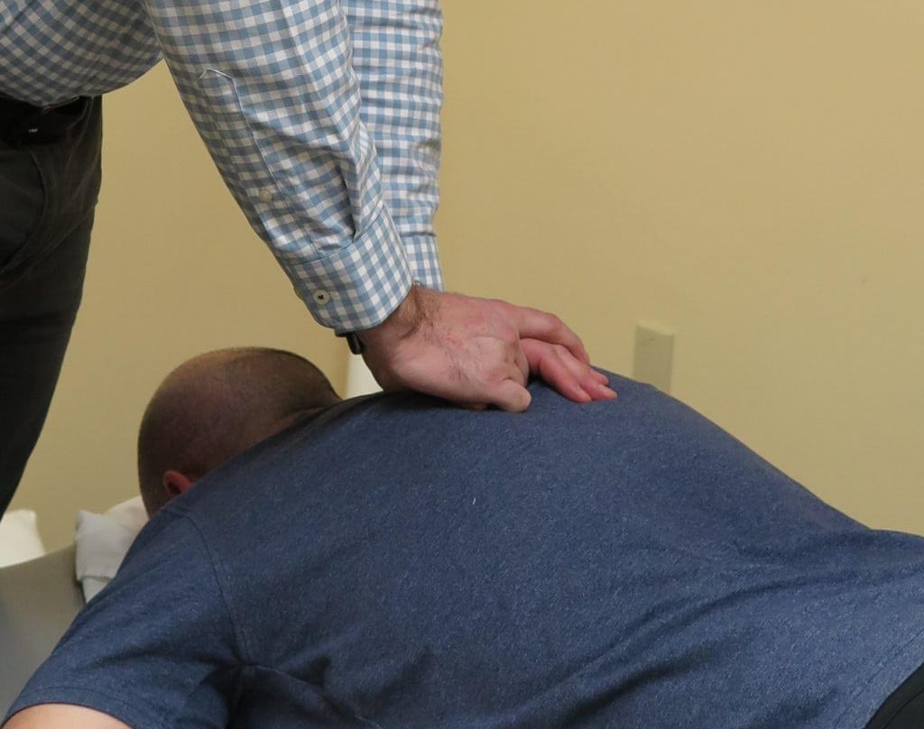 DPT performing manual therapy for lower back pain